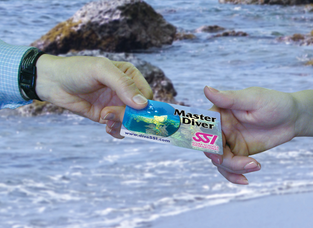photo of someone handing someone else a SSI Master Diver card